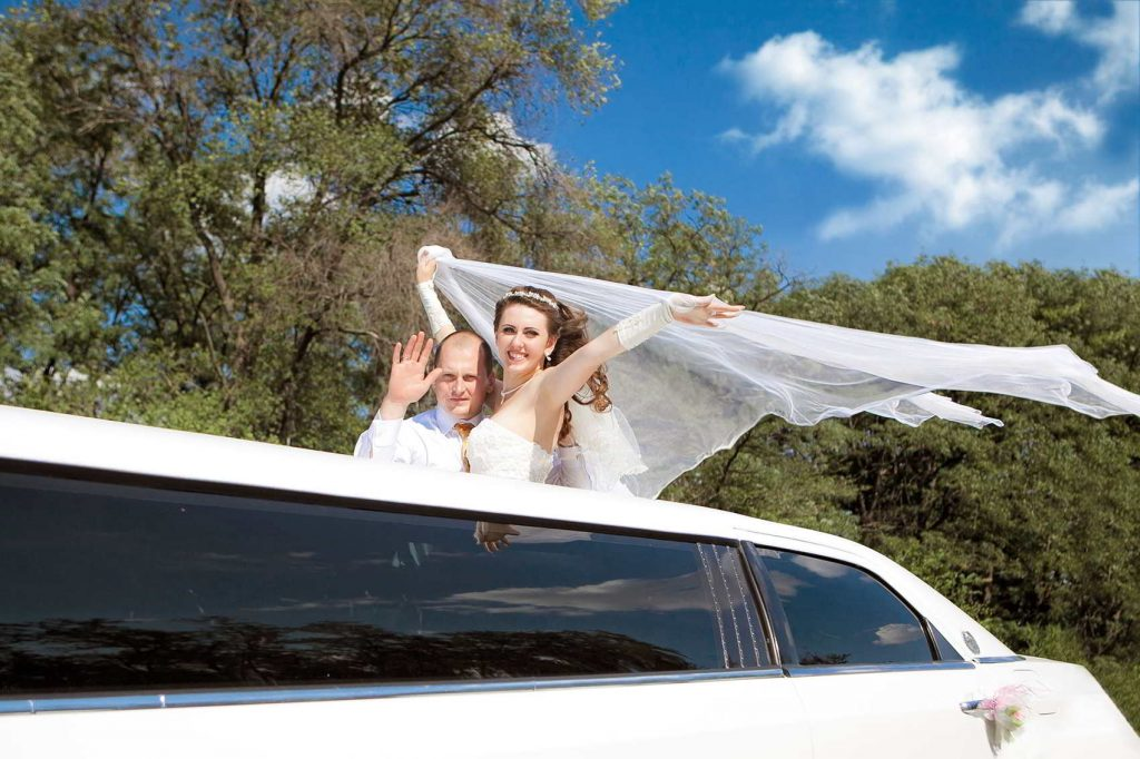 Wedding couple enjoying a ride in a 10-Passenger White Stretched Limo. wedding limousine Clearwater, Florida. We also have limos for bachelor / bachelorette parties in Clearwater, FL.